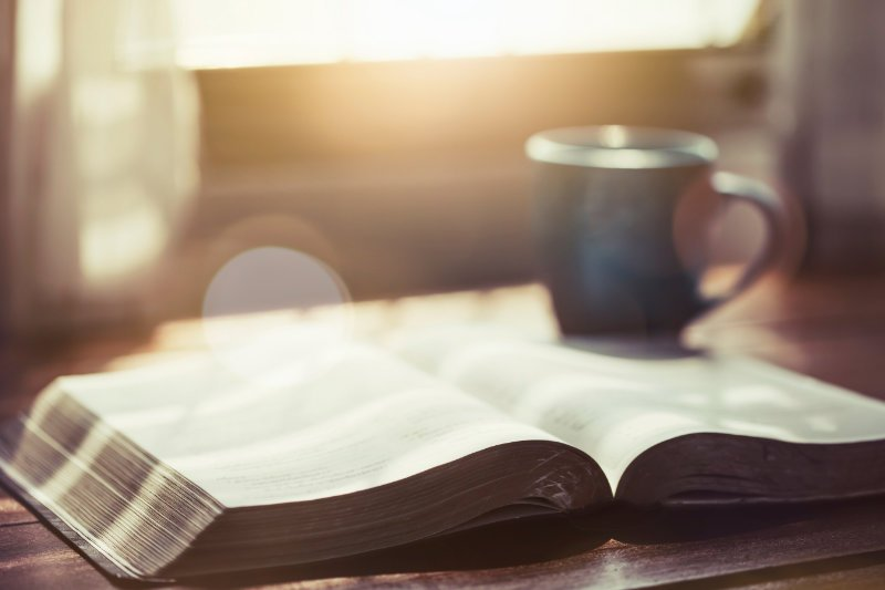 Boek met een kop koffie in de achtergrond