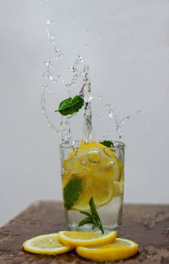 Glas citroenwater en een paar munt blaadjes erin