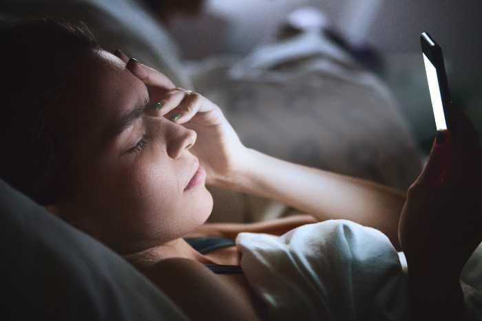 Vrouw die telefoon in bed gebruikt is slecht voor de slaapkwaliteit